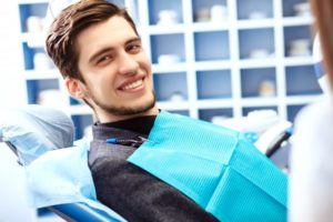 young man in dental chair smiling visiting dentist in plano